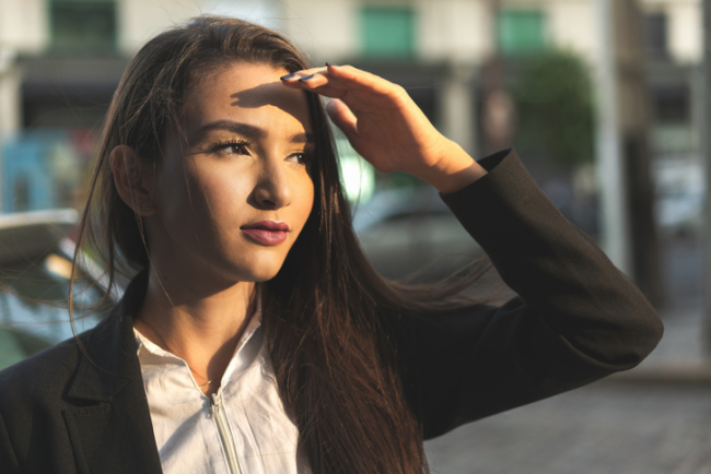 A Woman stood in the sun light and business suit with perfect Eyebrows & Lashes
