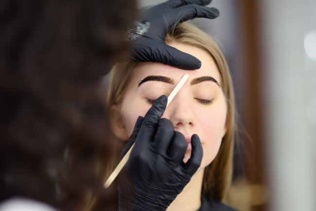 Cosmetologist making eyebrows design. Attractive woman getting facial care at beauty salon. Architecture eyebrows.