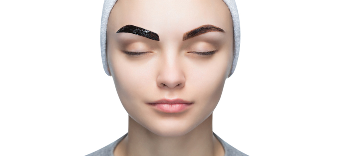 Portrait of a woman with beautiful, well-groomed eyebrows, makeup artist applies paint henna on eyebrows