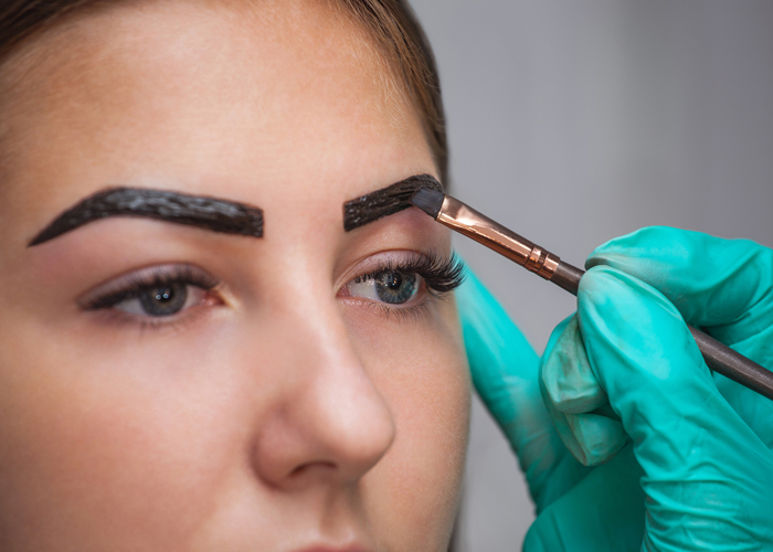 makeup artist applies paint henna on eyebrows.