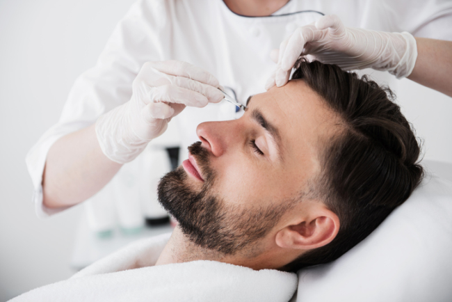 Careful cosmetologist plucking eyebrows of her calm client
