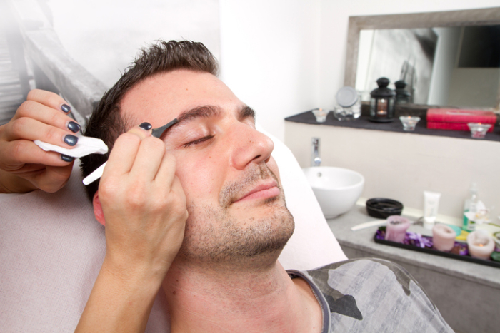 Beautician plucking a beautiful man eyebrows with tweezers