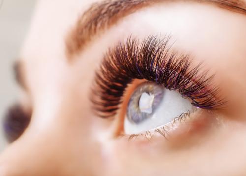 Eyelash Extension Procedure. Woman Eye with Long Eyelashes. Close up, selective focus