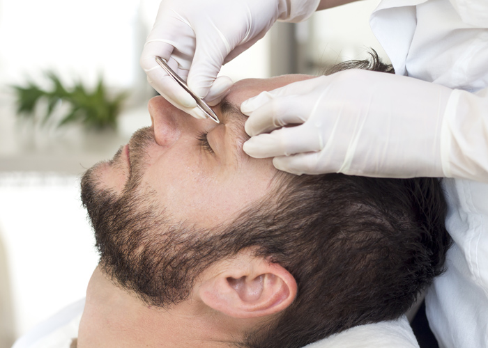Man in a beauty salon during the eyebrow adjustment procedure.